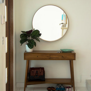Entryway - small 1960s marble floor entryway idea in Miami with white walls and a medium wood front door
