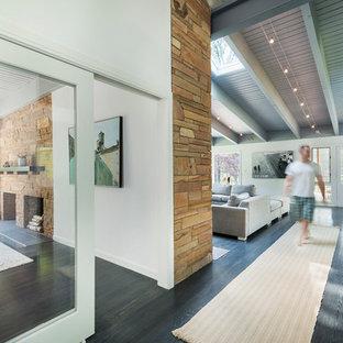 Bild på en stor 60 tals entré, med vita väggar, mörkt trägolv, en enkeldörr och grått golv