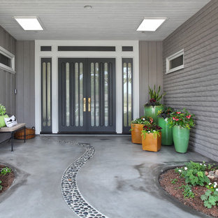 Inspiration for a mid-sized 1960s concrete floor entryway remodel in Orange County with gray walls
