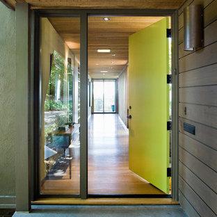 Modelo de puerta principal minimalista, grande, con puerta simple, puerta verde, paredes marrones y suelo de cemento