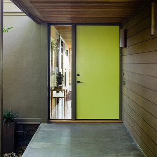 60 tals inredning av en stor ingång och ytterdörr, med bruna väggar, betonggolv, en enkeldörr och en grön dörr