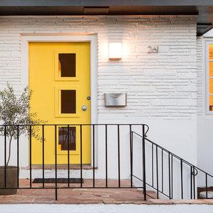 Aménagement d'une porte d'entrée rétro avec un mur blanc, un sol en ardoise, une porte simple et une porte jaune.