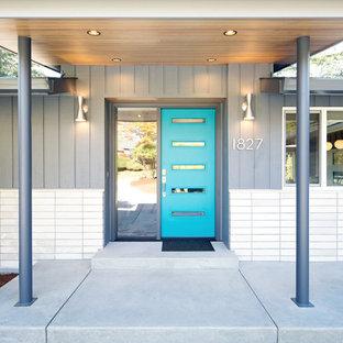 Modelo de puerta principal retro, de tamaño medio, con paredes grises, suelo de cemento, puerta simple, puerta azul y suelo gris