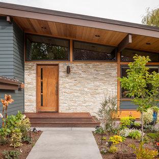 Immagine di una porta d'ingresso moderna di medie dimensioni con una porta singola e una porta in legno bruno