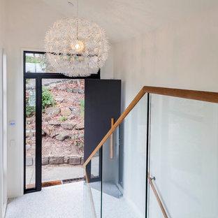メルボルンの広い片開きドアミッドセンチュリースタイルのおしゃれな玄関ドア (白い壁、テラゾーの床、黒いドア) の写真