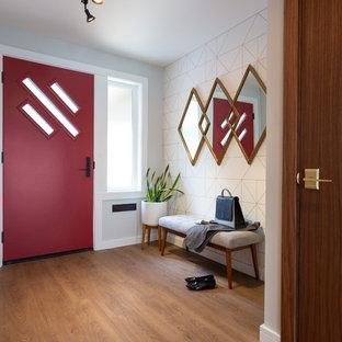 バンクーバーの小さい片開きドアミッドセンチュリースタイルのおしゃれな玄関ドア (グレーの壁、無垢フローリング、赤いドア、茶色い床) の写真