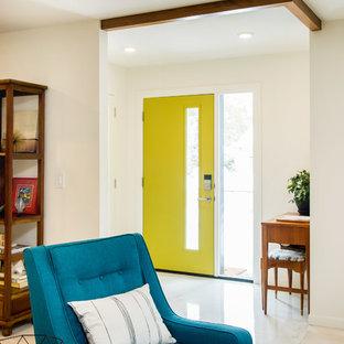 Bild på en liten retro ingång och ytterdörr, med vita väggar, ljust trägolv, en enkeldörr och en gul dörr