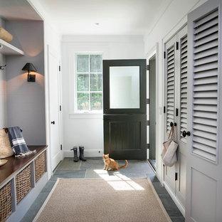 Foto på ett lantligt kapprum, med skiffergolv, en tvådelad stalldörr och en svart dörr