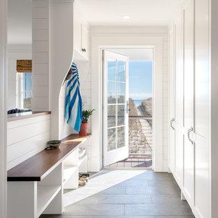 Aménagement d'une entrée bord de mer avec un vestiaire, un mur blanc, une porte simple, une porte en verre et un sol gris.