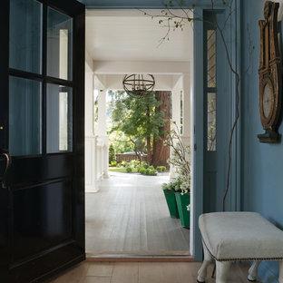 Immagine di un ingresso o corridoio tradizionale con una porta nera, pareti blu e pavimento beige