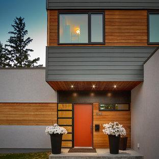 Ispirazione per una grande porta d'ingresso design con una porta singola, una porta rossa, pavimento in cemento e pavimento grigio
