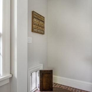 На фото: маленькая прихожая в стиле кантри с белыми стенами, кирпичным полом и красным полом с