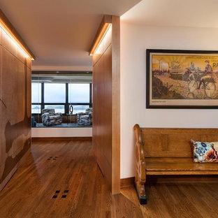 Idée de décoration pour une entrée tradition de taille moyenne avec un couloir, un mur blanc et un sol en bois brun.