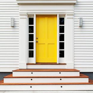Aménagement d'une porte d'entrée classique avec une porte simple et une porte jaune.