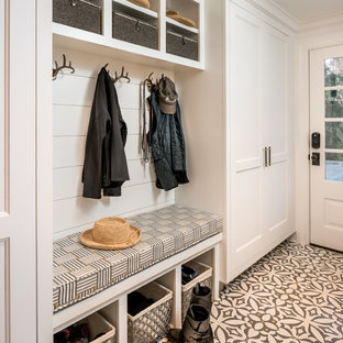 Example of a small coastal ceramic floor and multicolored floor entryway design in New York with white walls and a white front door