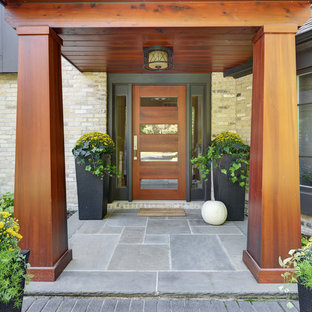 Inspiration for a mid-sized contemporary slate floor and gray floor entryway remodel in Milwaukee with a medium wood front door