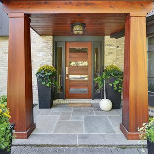Cette photo montre une porte d'entrée tendance de taille moyenne avec une porte simple, un sol en ardoise, une porte en bois brun et un sol gris.