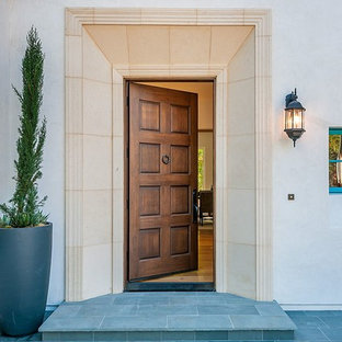 Example of a large tuscan slate floor entryway design in San Francisco with white walls and a medium wood front door
