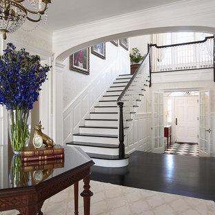 На фото: огромное фойе в классическом стиле с белыми стенами, темным паркетным полом, одностворчатой входной дверью, белой входной дверью и черным полом с