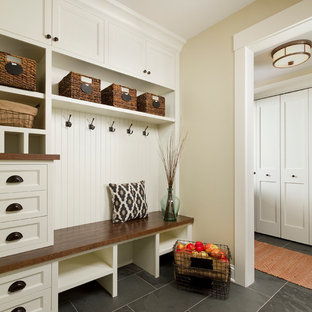 На фото: тамбур среднего размера со шкафом для обуви в классическом стиле с бежевыми стенами и полом из сланца