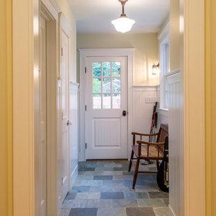 Imagen de puerta principal costera, grande, con suelo de pizarra, paredes amarillas, puerta simple y puerta blanca