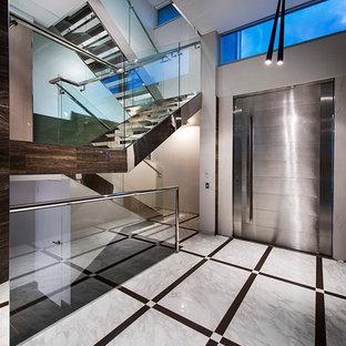 Стильный дизайн: фойе в современном стиле с бежевыми стенами, мраморным полом, поворотной входной дверью и металлической входной дверью - последний тренд
