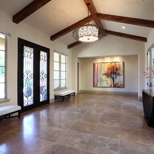 Réalisation d'un très grand hall d'entrée tradition avec une porte double, une porte métallisée, un mur beige et un sol en travertin.