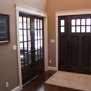 Idées déco pour un hall d'entrée craftsman de taille moyenne avec un mur marron, un sol en bois foncé, une porte simple et une porte en bois foncé.