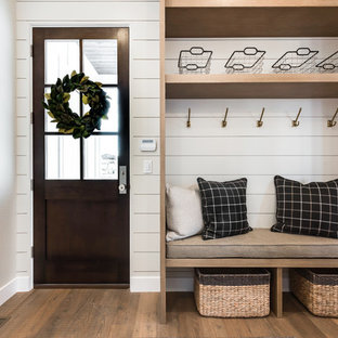 This is an example of a country mudroom in Salt Lake City with white walls, light hardwood floors, a single front door, a dark wood front door and brown floor.