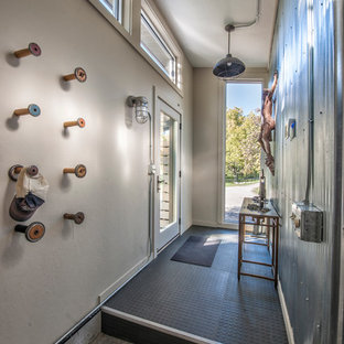 Example of an urban concrete floor entryway design in Other with white walls