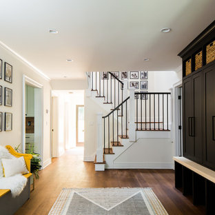 Inspiration for a small transitional medium tone wood floor and brown floor mudroom remodel in Raleigh with white walls