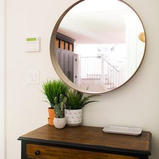 ローリーの小さい片開きドアトランジショナルスタイルのおしゃれな玄関ロビー (白い壁、無垢フローリング、黒いドア、茶色い床) の写真