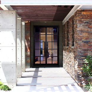 Ejemplo de puerta principal actual, grande, con paredes marrones, suelo de piedra caliza, puerta doble y puerta de vidrio