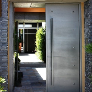 Example of a large trendy marble floor entryway design in Las Vegas with gray walls and a gray front door