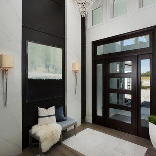 Cette photo montre un hall d'entrée chic avec un sol en bois brun, une porte simple et une porte en verre.