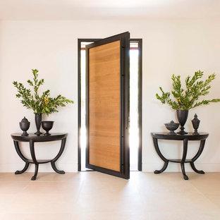 Ejemplo de entrada actual con paredes blancas, puerta pivotante, puerta de madera en tonos medios y suelo beige