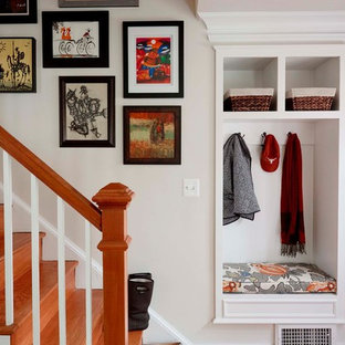 Example of a small classic medium tone wood floor and brown floor entryway design in Other with white walls