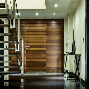 Example of a large minimalist ceramic floor and black floor entryway design in Los Angeles with a medium wood front door and white walls
