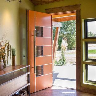 Modelo de puerta principal vintage, grande, con paredes verdes, suelo de madera en tonos medios, puerta simple, puerta naranja y suelo marrón