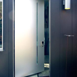 Foto på en mellanstor funkis ingång och ytterdörr, med vita väggar, betonggolv, en enkeldörr och metalldörr