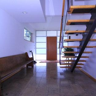 Idées déco pour un hall d'entrée contemporain avec un mur blanc, une porte simple et une porte en bois brun.