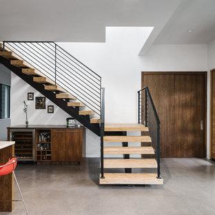 Создайте стильный интерьер: большая входная дверь в стиле модернизм с белыми стенами, бетонным полом, раздвижной входной дверью, входной дверью из светлого дерева и серым полом - последний тренд