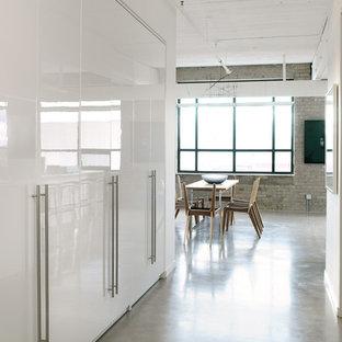 Industriell inredning av en stor hall, med vita väggar, betonggolv, en enkeldörr, en grå dörr och grått golv