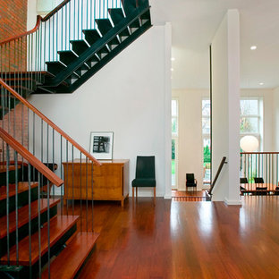 Trendy red floor entryway photo in New York with white walls