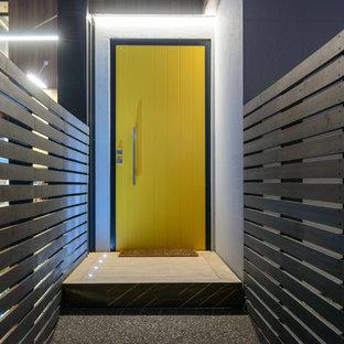 Ejemplo de puerta principal moderna, grande, con paredes blancas, suelo de cemento, puerta simple, puerta amarilla y suelo gris