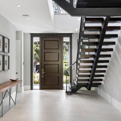 Example of a large trendy porcelain tile and white floor entryway design in Miami with gray walls and a dark wood front door