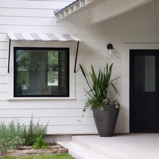 Foto på en lantlig entré, med en enkeldörr och en svart dörr