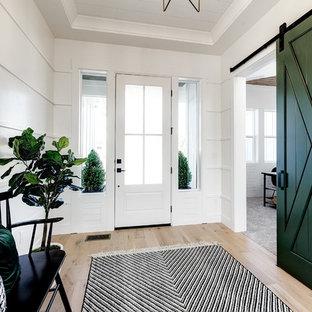 Réalisation d'un hall d'entrée champêtre de taille moyenne avec un mur blanc, un sol en bois clair, une porte simple, une porte blanche et un sol beige.