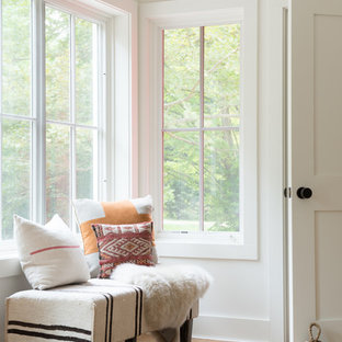 Small farmhouse light wood floor foyer photo in New York with white walls and a white front door