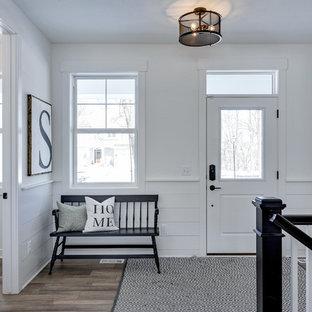 Bild på en mellanstor lantlig foajé, med vita väggar, laminatgolv, en enkeldörr, en vit dörr och brunt golv